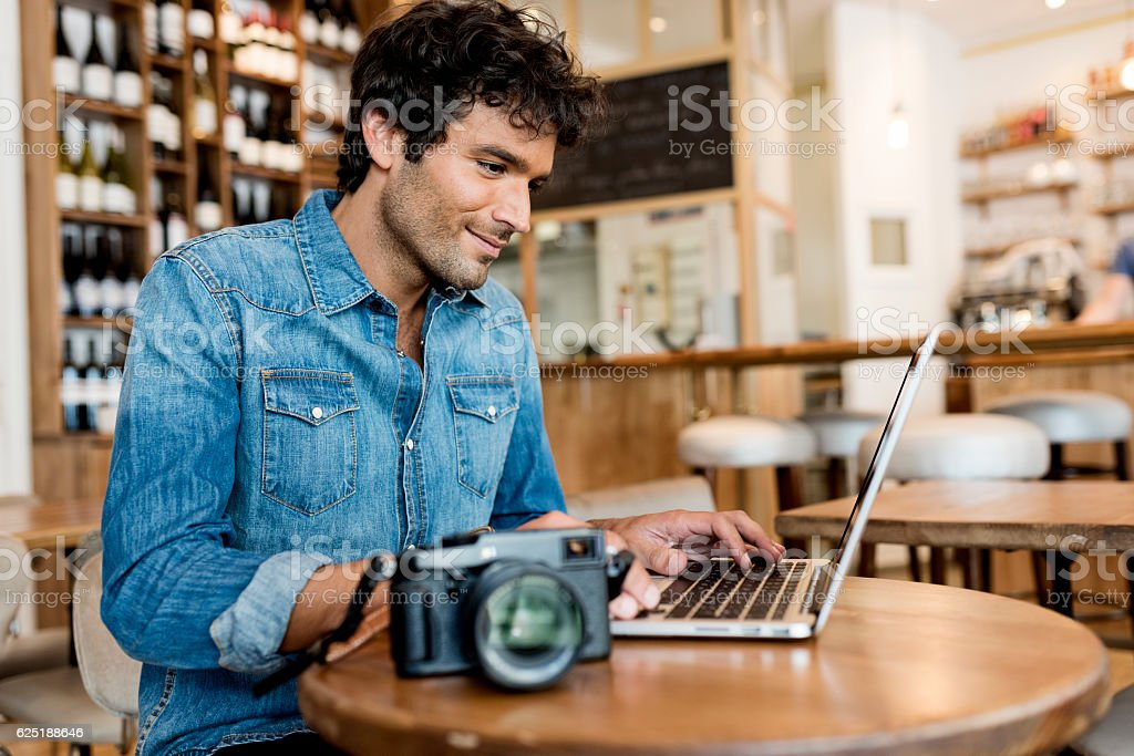 Man tourist looks at his pictures on computer stock photo