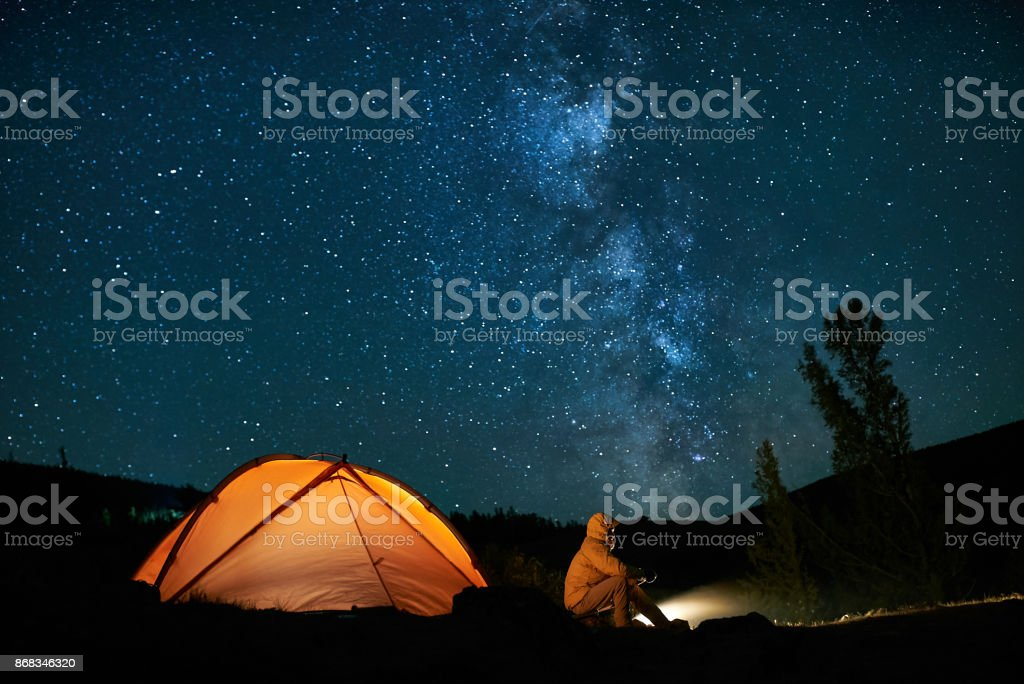 Man tourist near his camp tent at night. stock photo