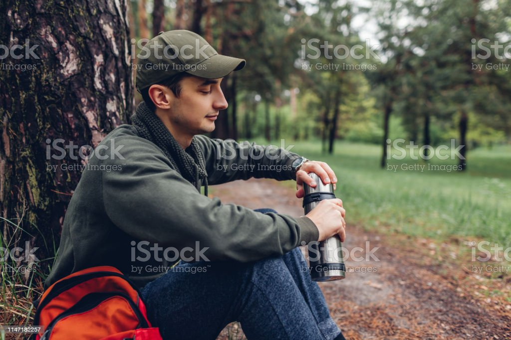 Man tourist opens thermos with hot tea in spring forest. Guy having...