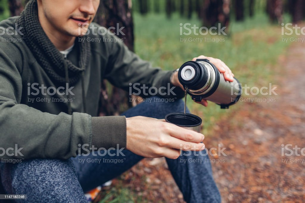 Man tourist pours hot tea out of thermos in spring forest. Camping,...