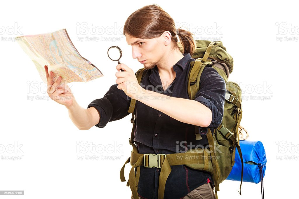 Man tourist reading map with magnifying glass royalty-free stock photo