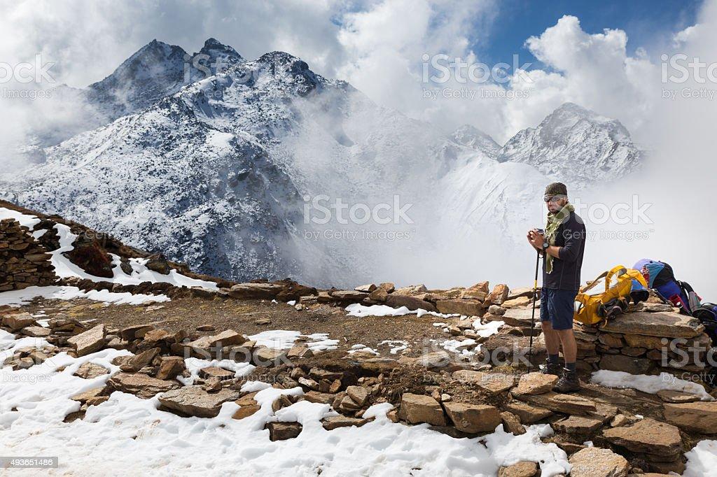 Man tourist standing in front snow mountain ridge peaks, Nepal. stock photo
