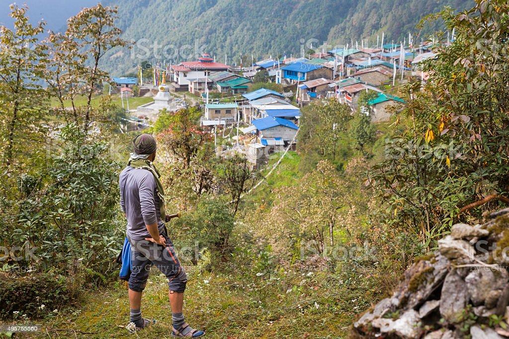 Man tourist warrior above mountain traditional nepalese village. stock photo
