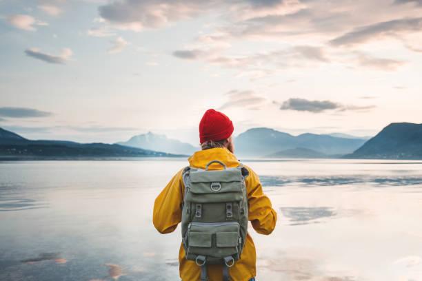Mann Tourist trägt gelbe Jacke und Rucksack vor dem Fjord stehen. Rückansicht von alleinWanderer am Küstenmeer zwischen Bergen – Foto
