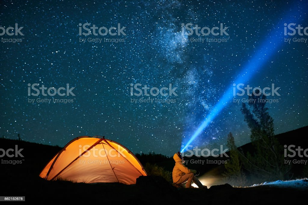 Man tourist with flashlight near his camp tent at night. stock photo