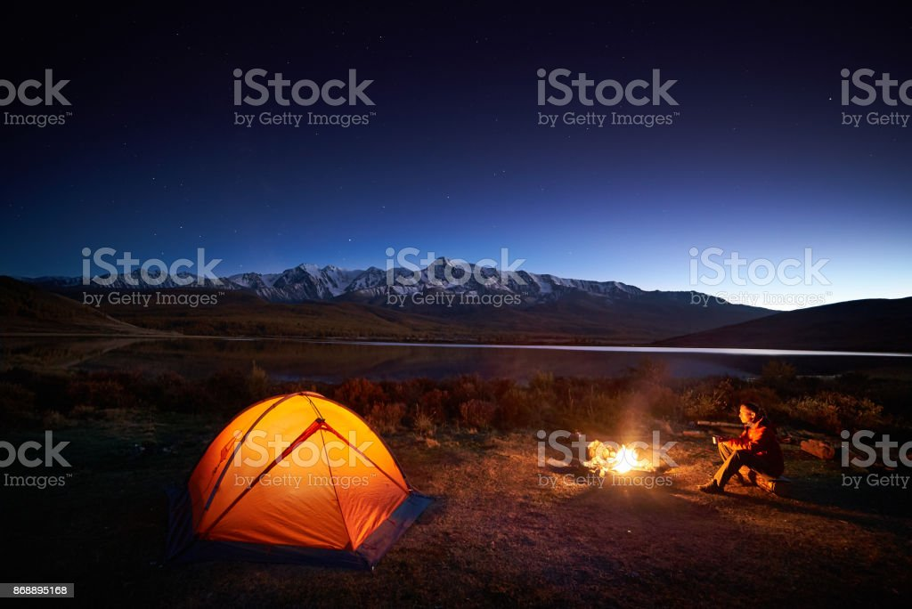 Man tourists sitting in the illuminated tent near campfire stock photo