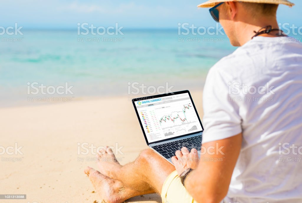 Man trading cryptocurrencies on the beach. Man trading cryptocurrencies on the beach. Concept of working anywhere. Adult Stock Photo