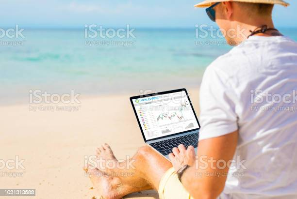 Man Trading Cryptocurrencies On The Beach Stock Photo - Download Image Now