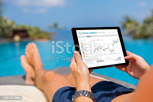 istock Man trading digital currencies online while relaxing by the pool. 1031313364