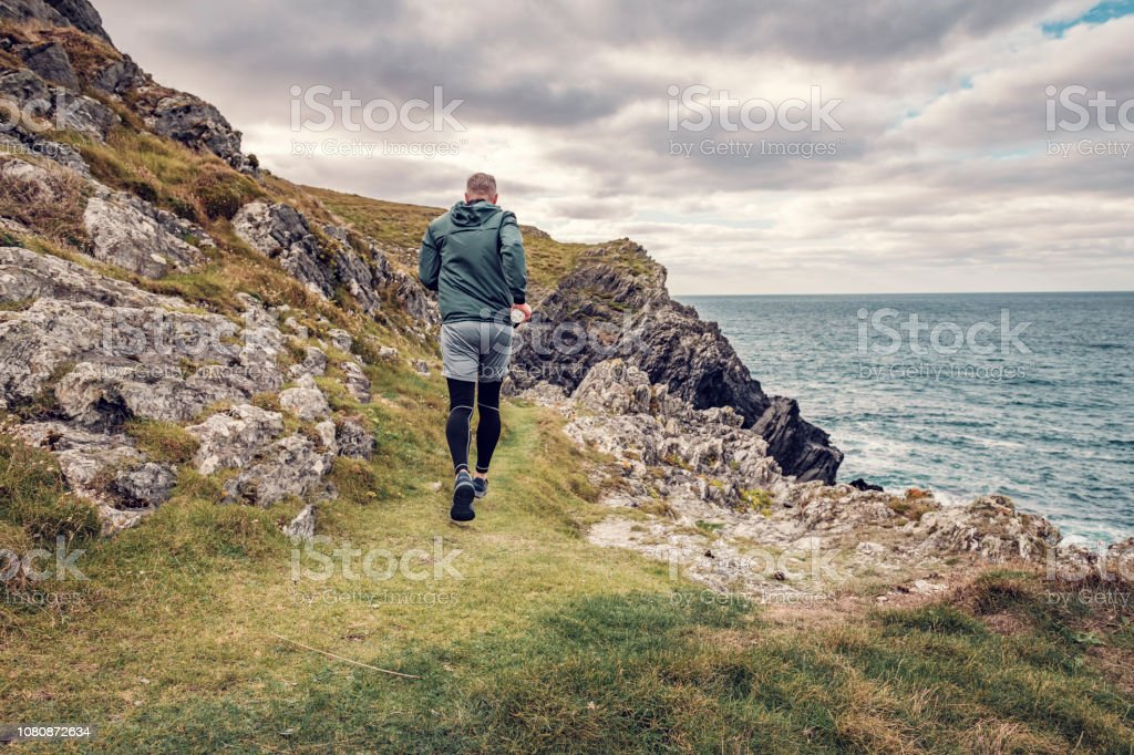 Man trail running along the rugged Cornish coastline on an Autumn day. stock photo
