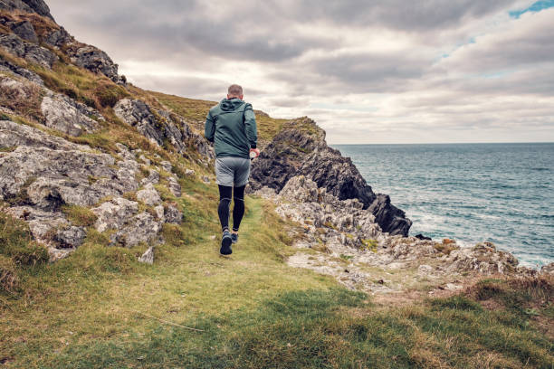 Man trail running along the rugged Cornish coastline on an Autumn day. stock photo