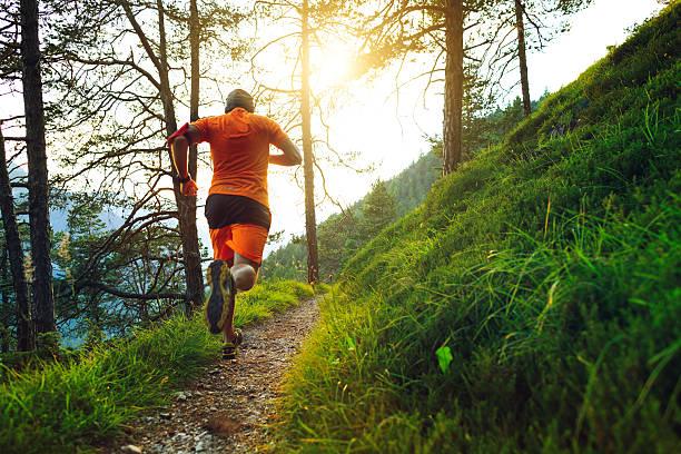 hombre corriendo en el bosque sendero - trail running fotografías e imágenes de stock