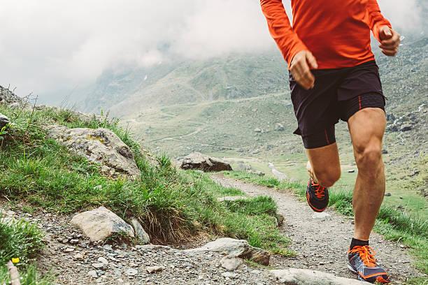 man trail running on a path in the mountain - laufveranstaltungen stock-fotos und bilder