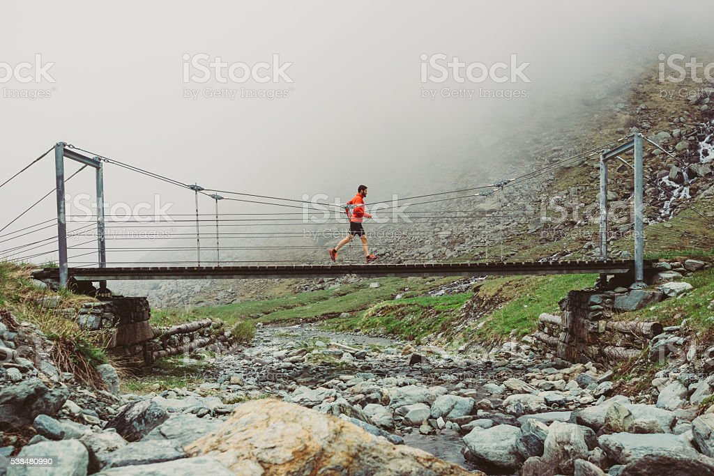 Man trail running on a path in the mountain stock photo