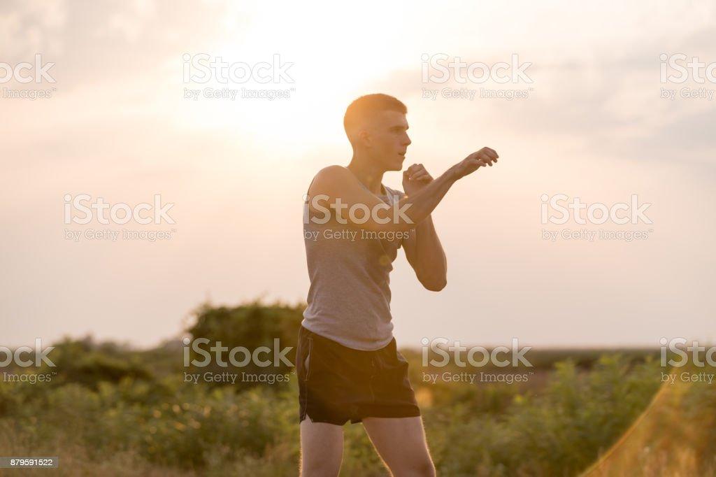 Man trainging shadow boxing outdoors stock photo