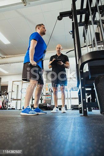 A low-down shot of a mid-adult caucasian man training in the gym, he is strengthening his triceps. A fitness instructor can be seen standing by the mans side motivating him.