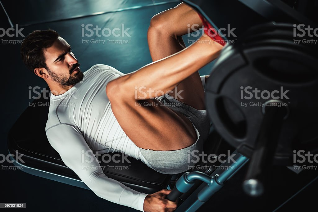 Man training legs on leg press machine stock photo
