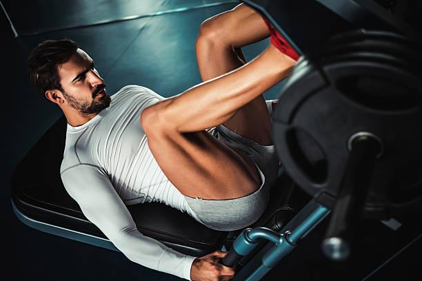 man training legs on leg press machine - human leg stock photos and pictures