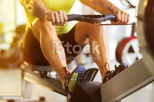 istock man training on row machine in gym 498693658