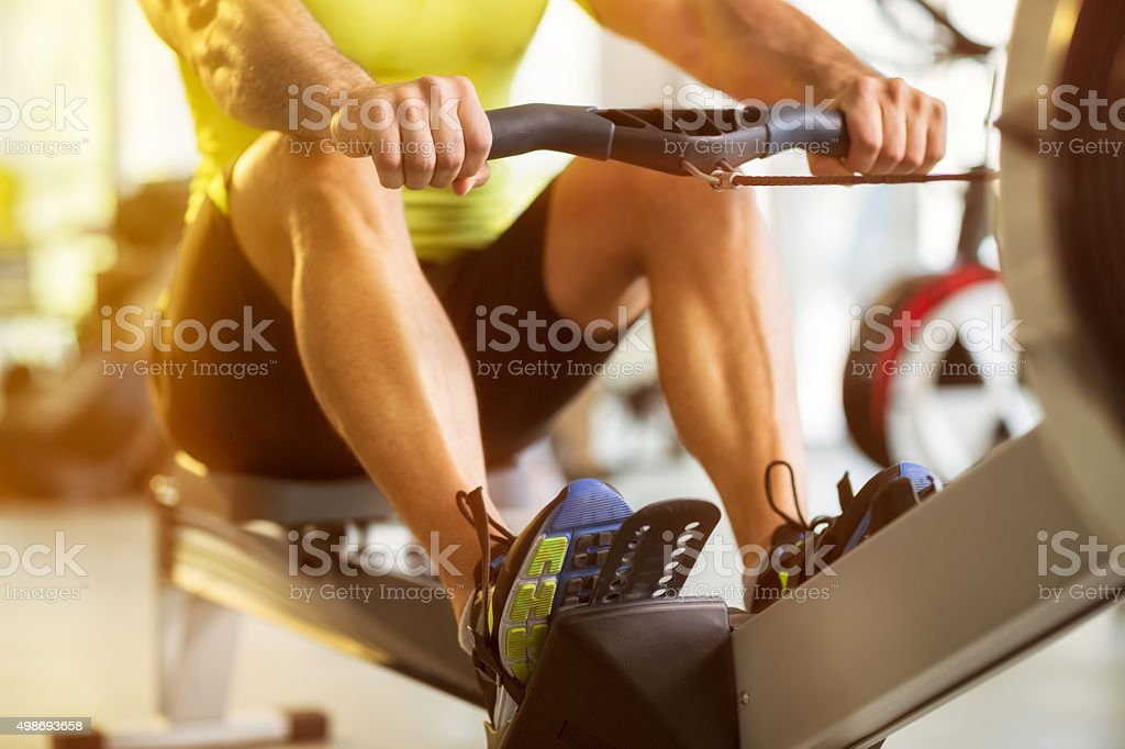 man training on row machine in gym stock photo