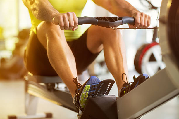man training on row machine in gym - exercise equipment stock photos and pictures