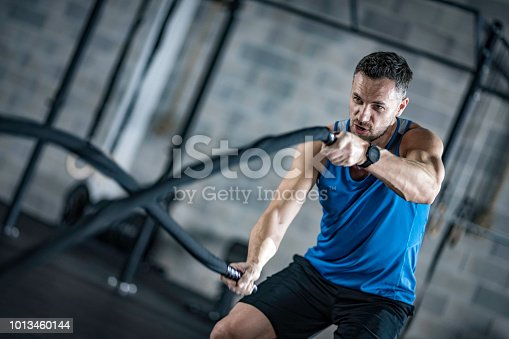 Photo of a man in a gym exercising by swinging battle ropes.