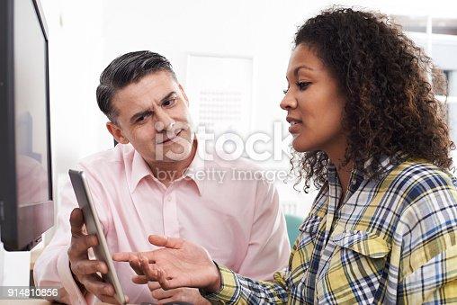 istock Man Training Woman In Office Using Digital Tablet 914810856