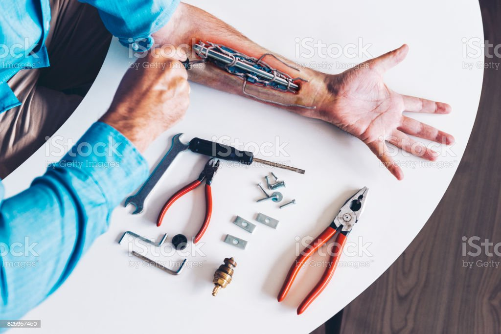 Man transforms into cyborg by implanting machine parts into robotic arm stock photo