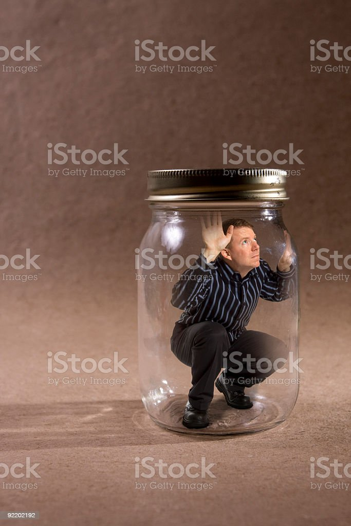 Man trapped in mason jar looking out (Concept Series) stock photo