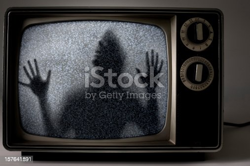 A frightening image of a man trapped inside a static-y retro television