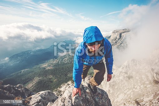 istock Man Traveler climbing on mountain summit over clouds Travel Lifestyle success concept adventure active vacations outdoor extreme sport 1032757556