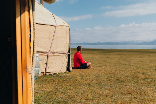 Young man in red shirt sitting at the meadow near the nomad yurts with mountain and lake view in Tian Shan, Central Asia