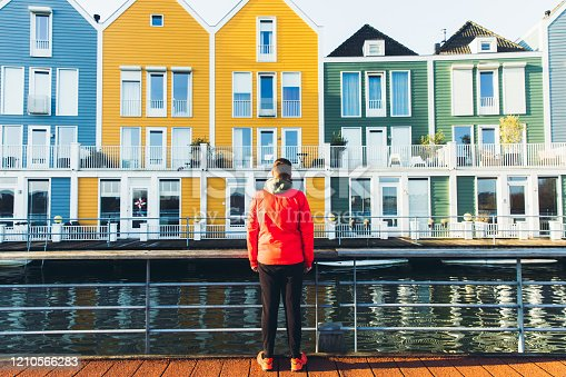 Young man tourist  in red jacket and eyeglasses walking at the bridge in small town near beautiful old-fashioned multi-colored houses during bright sunny day in Netherlands
