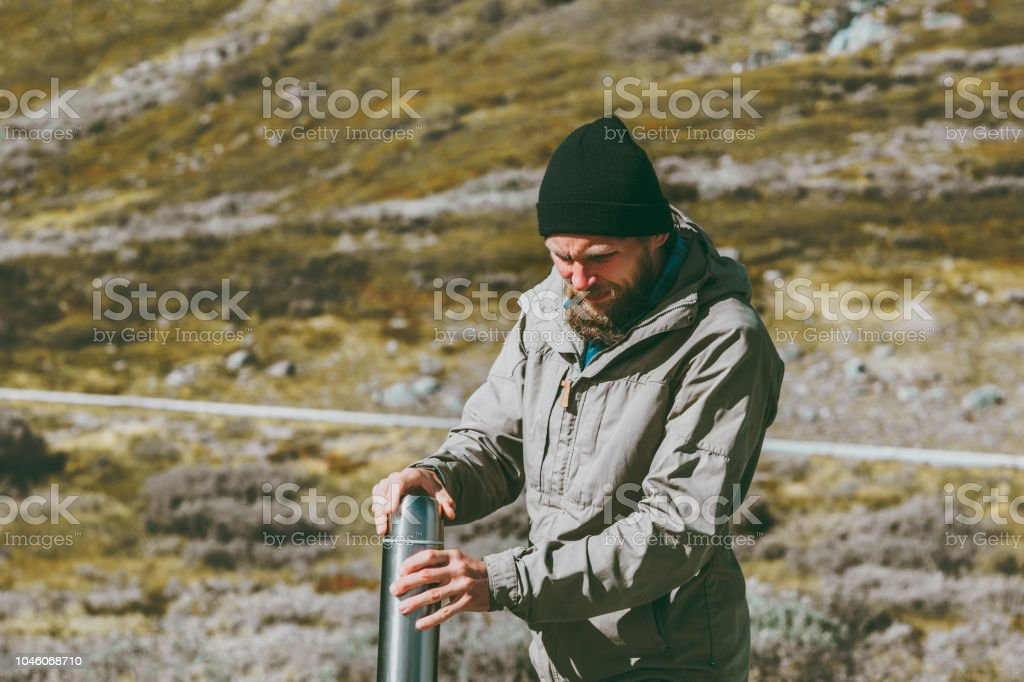 Man traveler holding thermos survival in mountains Travel lifestyle...