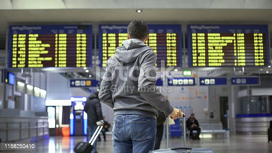 Man traveler looking at time table in train station, preparing for departure