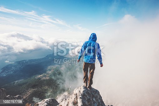 istock Man Traveler on mountain cliff enjoying aerial view over clouds Travel Lifestyle success concept adventure active vacations outdoor freedom emotions 1032757758