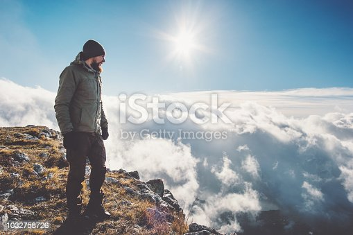 istock Man Traveler on mountain cliff over clouds Travel Lifestyle success concept adventure active vacations outdoor 1032758726
