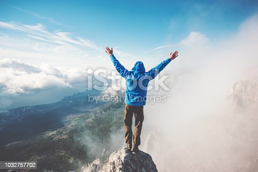 istock Man Traveler on mountain summit enjoying aerial view hands raised over clouds Travel Lifestyle success concept adventure active vacations outdoor happiness freedom emotions 1032757702