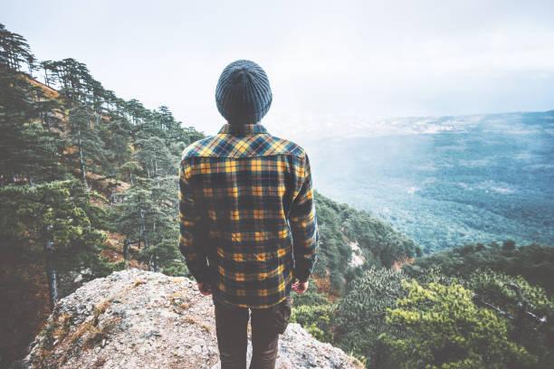 Mann Traveler Travel Fashion Lifestyle Abenteuer Urlaub Konzept auf Klippe allein Luftbild Wald Berge im Hintergrund stehend – Foto