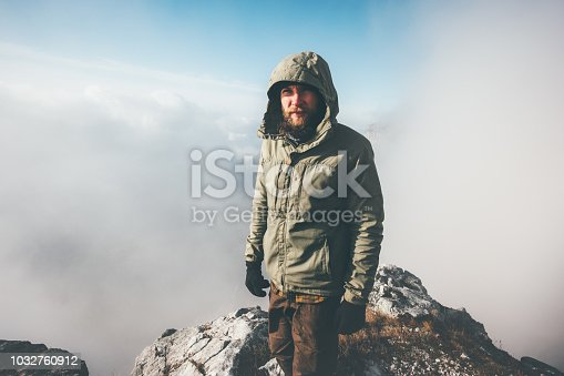 istock Man Traveler standing on mountain summit with clouds around Travel Lifestyle success concept adventure active vacations outdoor 1032760912