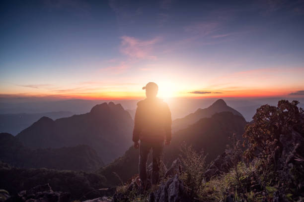 Man traveler standing on rock ridge with sunlight in wildlife sanctuary Man traveler standing on rock ridge with sunlight in wildlife sanctuary at sunset taoism stock pictures, royalty-free photos & images