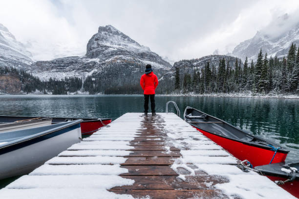 Man traveler standing on wooden pier with red canoe and snowing in Lake O'hara at Yoho national park stock photo
