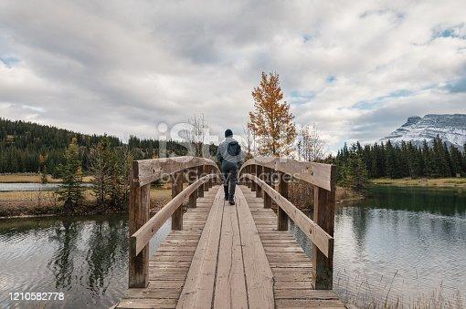 Man traveler walking cross over wooden bridge in autumn at Cascade Ponds, Banff national park, Canada