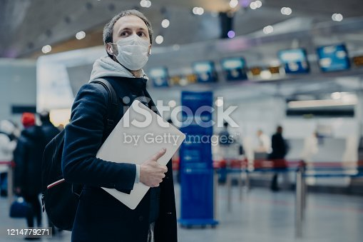 Man traveler wears protective disposable medical mask in airport, returns from abroad where coronavirus spreading, carries backpack, takes care of health, protects from virus, has postponed flight