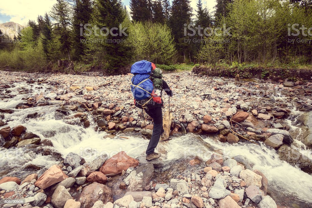 Man traveler with backpack crosses a mountain river. Vintage image stock photo