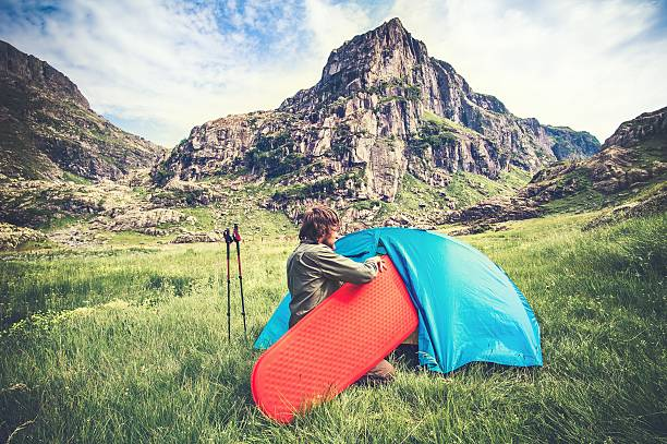 Man Traveler with camping equipment mattress and tent outdoor – Foto