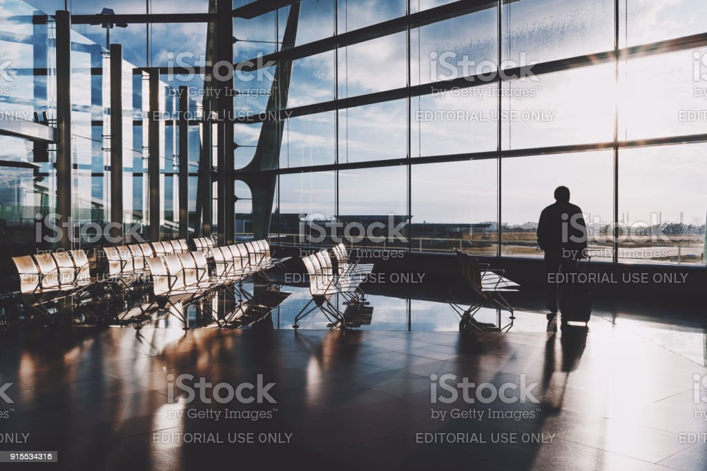 Man traveler with luggage bag near airport window stock photo