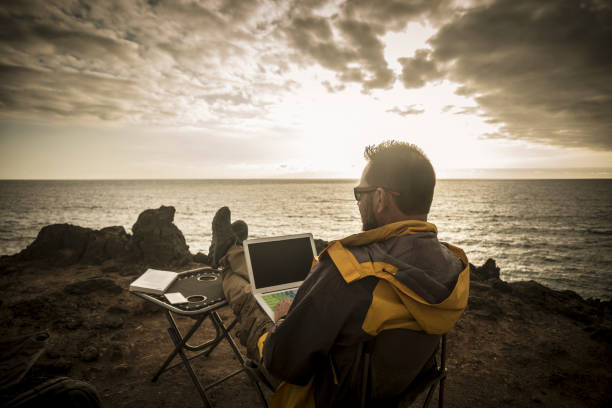 man traveler working during the sunset on a cliff with the ocean and the sun in front of him, freedom from office doing business everywhere like a digital nomad enjoying freedom and discovering the world stock photo