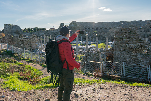 Man traveling alone taking photo with smartphone in Side Turkey