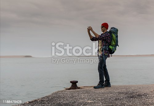 Man Traveling Backpack enjoying the beautiful view of the lake